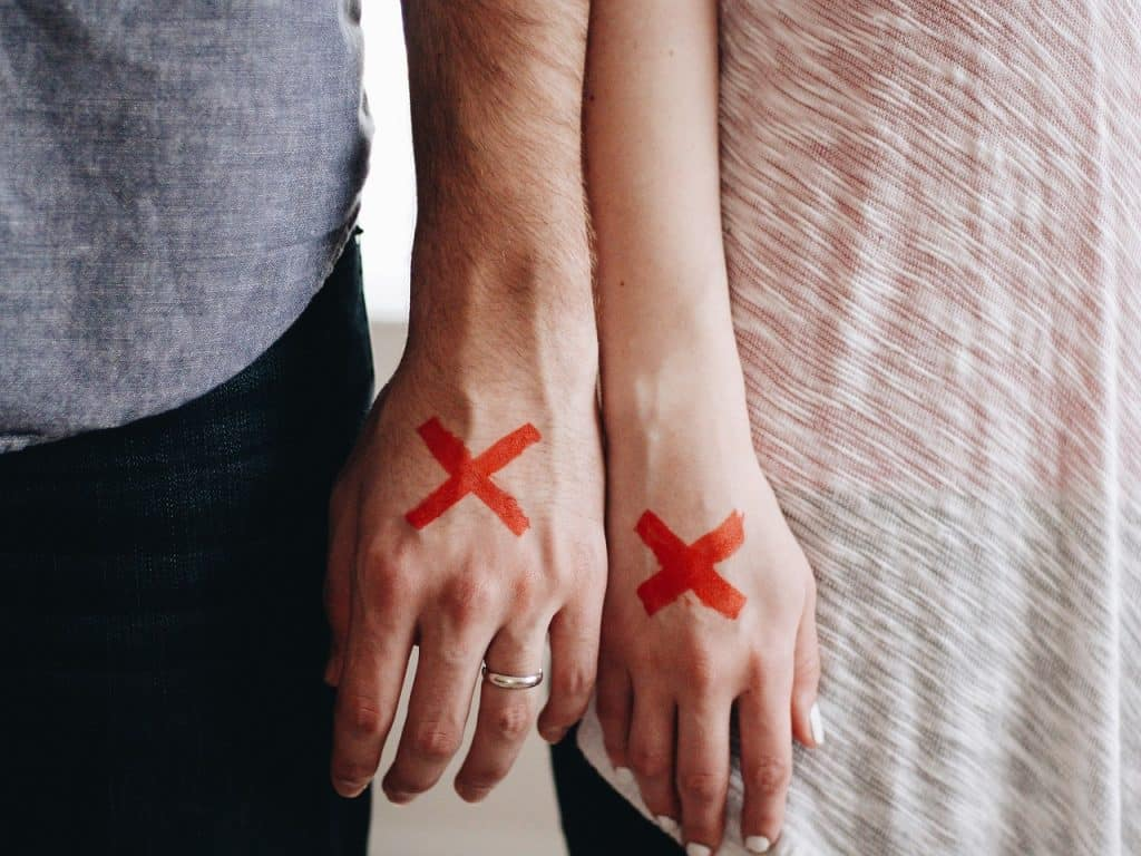 Hands of a couple with X on them