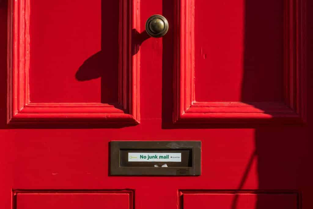 Red door with spam blocker sign